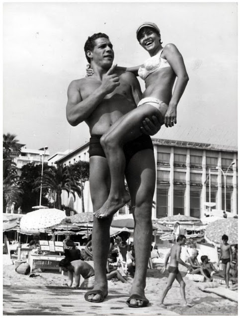 13. André on the 'Croisette', the beach boulevard in Cannes, France with a young lady in bikini, 29 July 1967.